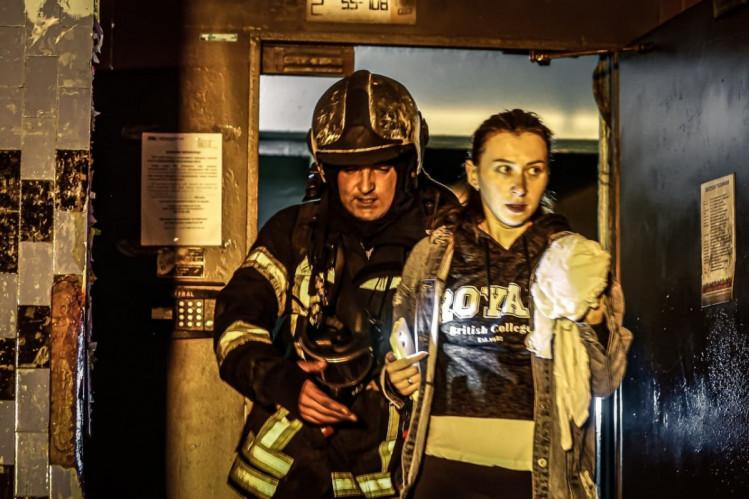 Пожежник виводить жінку